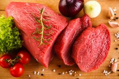 Fresh raw beef on cutting board and vegetables. On wooden table Stock Images