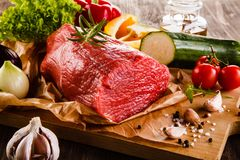 Fresh raw beef on cutting board and vegetables. On wooden table Royalty Free Stock Image