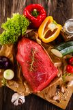 Fresh raw beef on cutting board and vegetables. On wooden table Stock Image