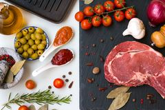 Fresh raw beef entrecote with ingredients to cooking taesty dinner . A fresh raw beef entrecote with ingredients to cooking taesty dinner Royalty Free Stock Photos