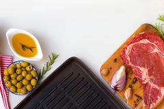 Fresh raw beef entrecote with ingredients to cooking taesty dinner and frying pan, top view with space for text. A fresh raw beef entrecote with ingredients to Stock Images