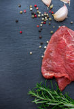 Fresh raw beef. From the farmers market on a black grunge table. Selective focus, flat lay, copy space Stock Images