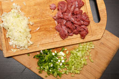 Fresh raw beef with green onions. And celery cut into pieces on a cutting board Royalty Free Stock Photos
