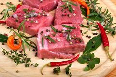 Fresh raw beef meat close up. With color peppercorn and rosemary on cutting board Royalty Free Stock Photography