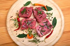 Fresh raw beef meat. With color peppercorn and rosemary on a round cutting board Royalty Free Stock Images