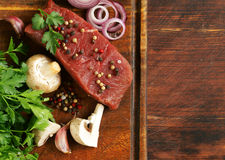 Fresh raw beef meat on a cutting board with vegetables. And spices Royalty Free Stock Image