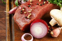 Fresh raw beef meat on a cutting board with vegetables. And spices Stock Images