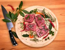 Fresh raw beef meat. With color peppercorn and rosemary on a round cutting board Royalty Free Stock Photo
