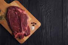 Fresh raw beef meat. Steaks in the black plate with spices on black wooden background Stock Images