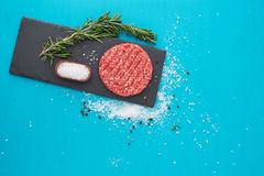 Fresh raw beef meat with herbs and salt on turquoise background. Flat lay composition of raw beef meat with rosemary, black bell pepper and coarse salt on light Royalty Free Stock Images