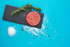 Fresh raw beef meat with herbs and salt on turquoise background. Flat lay composition of raw beef meat with rosemary, black bell pepper and coarse salt on light Royalty Free Stock Photo