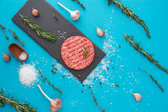 Fresh raw beef meat with herbs and salt on turquoise background. Flat lay composition of raw beef meat with rosemary, thyme, garlic, black bell pepper and Royalty Free Stock Images