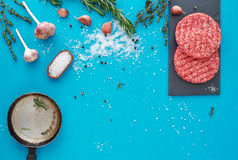Fresh raw beef meat with herbs and salt on turquoise background. Flat lay composition of raw beef meat with rosemary, thyme, garlic, black bell pepper and Stock Photography