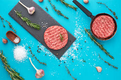 Fresh raw beef meat with herbs and salt on turquoise background. Flat lay composition of raw beef meat with rosemary, thyme, garlic, black bell pepper and Stock Photo