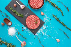 Fresh raw beef meat with herbs and salt on turquoise background. Flat lay composition of raw beef meat with rosemary, thyme, garlic, black bell pepper and Royalty Free Stock Photos