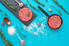 Fresh raw beef meat with herbs and salt on turquoise background. Flat lay composition of raw beef meat with rosemary, thyme, garlic, black bell pepper and Stock Photos