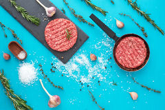 Fresh raw beef meat with herbs and salt on turquoise background. Flat lay composition of raw beef meat with rosemary, thyme, garlic, black bell pepper and Royalty Free Stock Photography