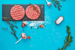 Fresh raw beef meat with herbs and salt on turquoise background. Flat lay composition of raw beef meat with rosemary, thyme, garlic, black bell pepper and Royalty Free Stock Photo