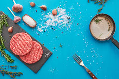 Fresh raw beef meat with herbs and salt on turquoise background. Flat lay composition of raw beef meat with rosemary, thyme, garlic, black bell pepper and Royalty Free Stock Image
