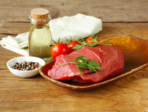 Fresh raw beef meat with pepper and herbs. On wooden plate Royalty Free Stock Images