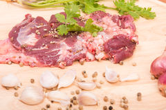 Fresh raw beef meat slices and garlic, pepper on wooden Stock Images