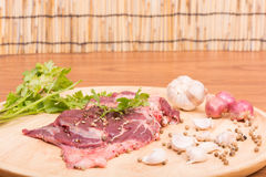 Fresh raw beef meat slices and garlic, pepper on wooden Stock Photos