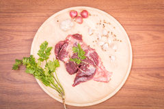 Fresh raw beef meat slices and garlic, pepper on wooden. Ready to cooking on wood table Royalty Free Stock Photo