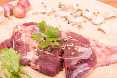 Fresh raw beef meat slices and garlic, pepper on wooden. Ready to cooking on wood table Stock Photography