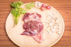 Fresh raw beef meat slices and garlic, pepper on wooden. Ready to cooking on wood table Royalty Free Stock Photography
