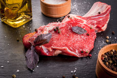 Fresh raw beef meat with spices. Fresh raw beef meat on a black slate stone background. With spices for cooking, copy space, close view Royalty Free Stock Photos