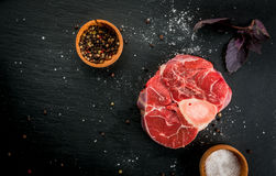 Fresh raw beef meat with spices. Fresh raw beef meat on a black slate stone background. With spices for cooking, copy space, top view Royalty Free Stock Photo