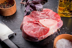 Fresh raw beef meat with spices. Fresh raw beef meat on a black slate stone background. With spices for cooking and knife, copy space Royalty Free Stock Photo