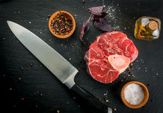 Fresh raw beef meat with spices. Fresh raw beef meat on a black slate stone background. With spices for cooking and knife, copy space, top view Royalty Free Stock Image
