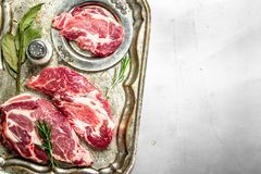 Fresh raw beef meat with spices and herbs. On rustic background Stock Photography