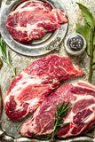 Fresh raw beef meat with spices and herbs. On rustic background Stock Images