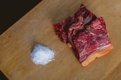 Fresh raw beef meat steak slices on wooden cut board and fat salt stock image