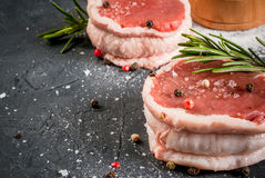 Fresh raw beef medallions. On a cutting board with a knife and spices. In the dark gray stone table Stock Photos