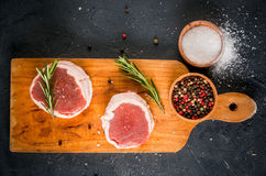 Fresh raw beef medallions. On a cutting board with a knife and spices. In the dark gray stone table. Top view Royalty Free Stock Photos