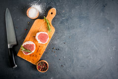 Fresh raw beef medallions. On a cutting board with a knife and spices. In the dark gray stone table. Top view, copy space Royalty Free Stock Image