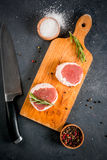 Fresh raw beef medallions. On a cutting board with a knife and spices. In the dark gray stone table. Top view, copy space Stock Photo