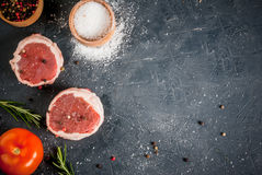 Fresh raw beef medallions. On a cutting board with a knife and spices. In the dark gray stone table. Top view, copy space Stock Image