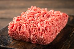 Fresh raw beef minced meat. On dark wooden board. Healthy food ingredients concept Stock Photos