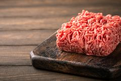 Fresh raw beef minced meat. On dark wooden board. Healthy food ingredients concept with copy space Royalty Free Stock Images