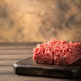 Fresh raw beef minced meat. On dark wooden board. Healthy food ingredients concept with copy space Stock Images