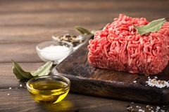 Fresh raw beef minced meat. With salt, pepper, olive oil and laurel leaves on dark wooden board. Healthy food concept with copy space Royalty Free Stock Image