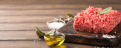 Fresh raw beef minced meat. With salt, pepper, olive oil and laurel leaves on dark wooden board. Healthy food concept with copy space Royalty Free Stock Photos