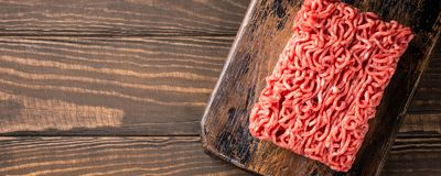 Fresh raw beef minced meat. Overhead shoot of fresh raw beef minced meat on dark wooden board. Healthy food ingredients concept with copy space. Top view. Banner Stock Photography