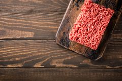 Fresh raw beef minced meat. Overhead shoot of fresh raw beef minced meat on dark wooden board. Healthy food ingredients concept with copy space. Top view Royalty Free Stock Photo