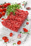 Fresh Raw Beef Minced Meat with salt, pepper, chilli and fresh thyme on white board. Fresh Raw Beef Minced Meat with salt, pepper, chilli and fresh thyme on Royalty Free Stock Image