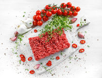 Fresh Raw Beef Minced Meat with salt, pepper, chilli and fresh thyme on white board. Fresh Raw Beef Minced Meat with salt, pepper, chilli and fresh thyme on Royalty Free Stock Photography